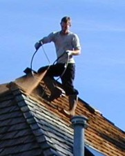 image of roof contractor cleaning a seattle home's roof